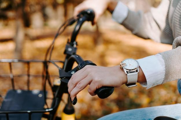 Andar de bicicleta em um dia ensolarado no outono park. mão feminina em uma roda de bicicleta