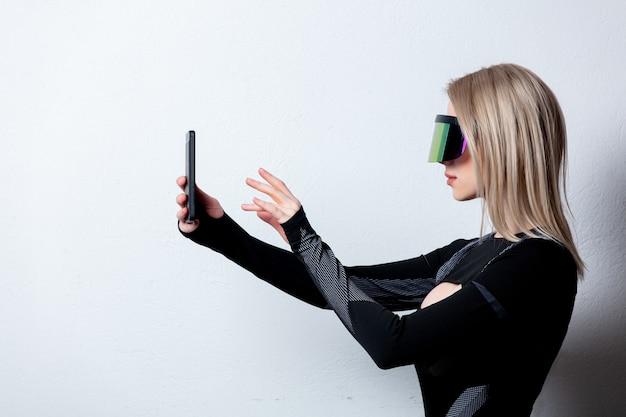 Android feminino em óculos de vr e telefone celular em fundo branco.