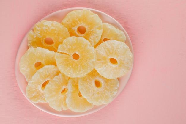 Anéis de abacaxi cristalizadas em um prato em uma superfície rosa