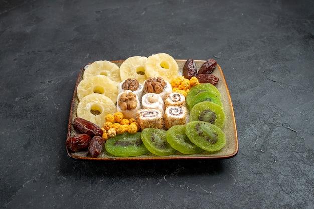 Anéis de abacaxi em fatias de frutas secas e kiwis em um espaço cinza
