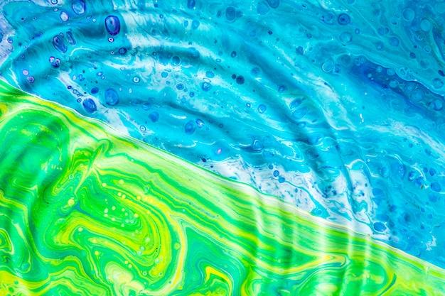 Anéis de água de close-up na superfície verde e azul