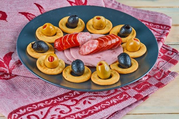 Anéis de biscoito e fatias de salsichas com azeitonas em um prato de cerâmica com toalha de mesa rosa.