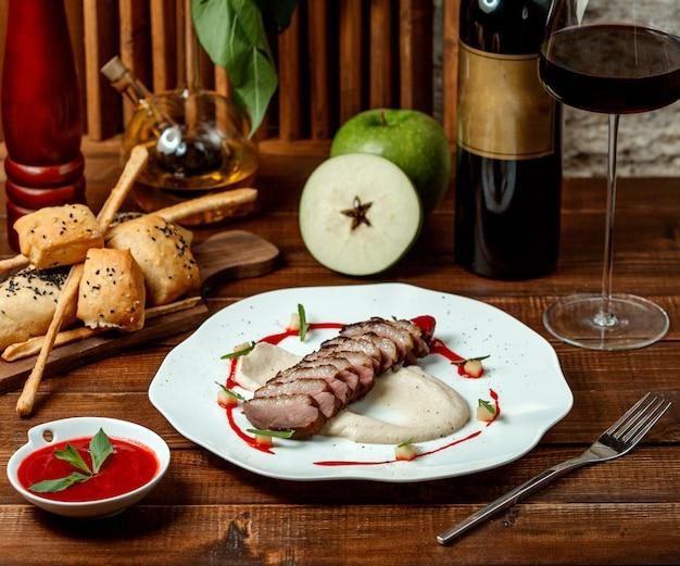 Anéis de carne com molho de maçã e um copo de vinho tinto