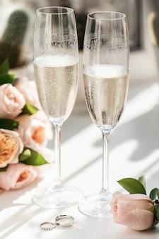 Anéis de casamento ao lado de duas taças de champanhe e um buquê de rosas