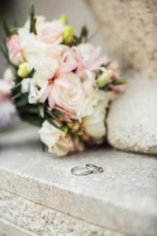 Anéis de casamento bonitos em uma superfície de pedra e buquê de flores