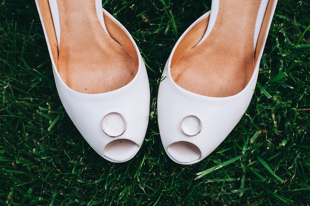 Anéis de casamento close-up em sapatos da noiva.