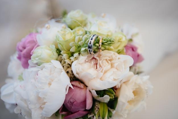 Anéis de casamento close-up no buquê de casamento bonito. acessórios de casamento.