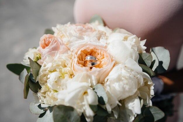 Anéis de casamento close-up no buquê de casamento bonito.