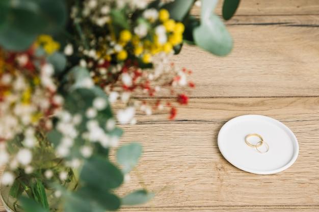 Anéis de casamento com buquê de flores