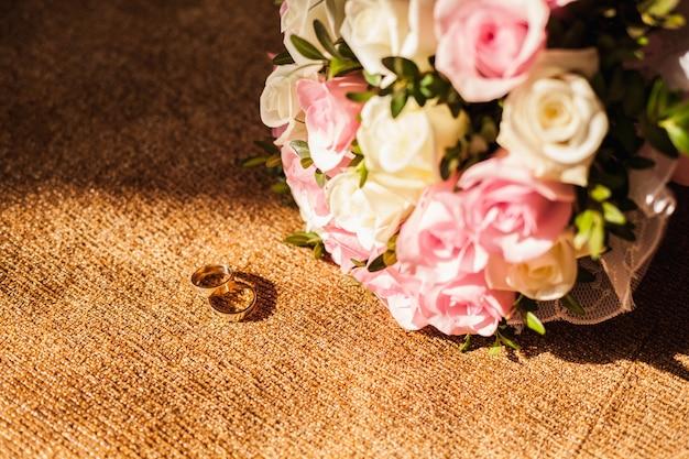 Anéis de casamento com buquê de rosas cor de rosa
