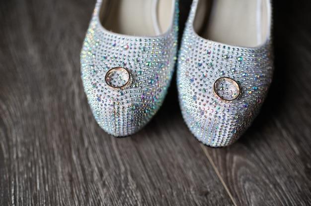 Anéis de casamento com diamantes no fundo dos sapatos de luxo de noiva, close-up