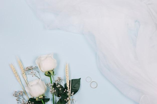 Anéis de casamento com flores e véu de noiva