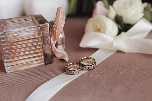 Anéis de casamento com gravura na fita cremosa, perfume e flores brancas