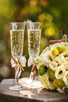 Anéis de casamento com rosas e taças de champanhe