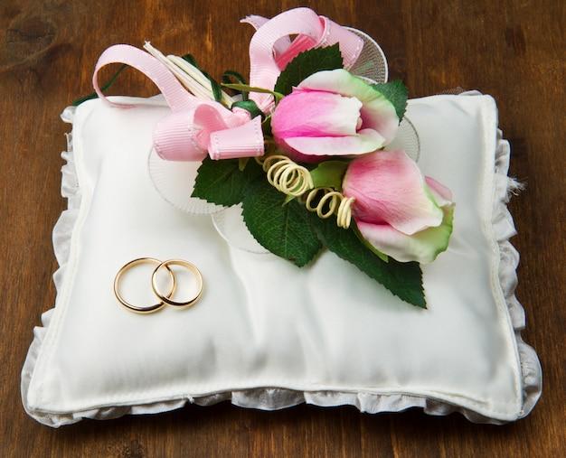 Anéis de casamento com rosas no travesseiro de noiva