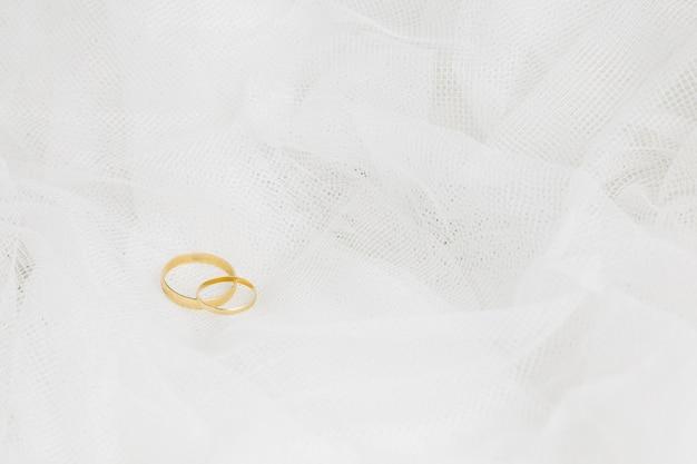 Anéis de casamento com véu de noiva