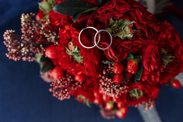 Anéis de casamento de ouro branco clássico no buquê vermelho