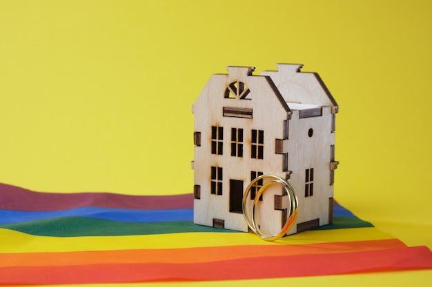 Anéis de casamento e modelo de casa de madeira e bandeira lgbtq