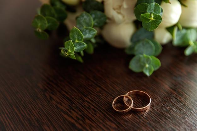 Anéis de casamento mentem na superfície de madeira contra o fundo do buquê de flores