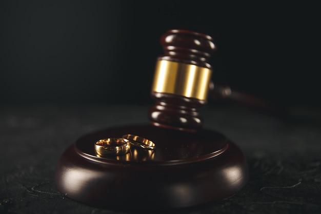 Anéis de casamento na placa de madeira e martelo do juiz