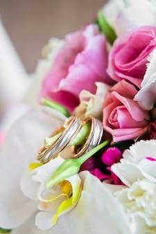 Anéis de casamento no buquê da noiva de rosas e coalas.