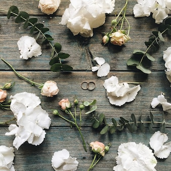 Anéis de casamento, rosas, hortênsias brancas e ramos isolados na velha mesa de menta de madeira retrô
