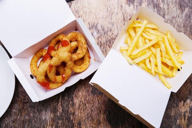 Anéis de cebola e batatas fritas em caixas