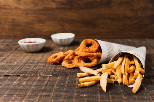 Anéis de cebola e batatas fritas na mesa de madeira