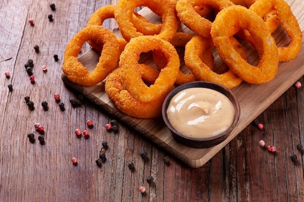 Anéis de cebola fritos crocantes caseiros deliciosos com molho picante. copie o espaço