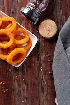 Anéis de cebola fritos crocantes caseiros deliciosos com molho picante. vista do topo. copie o espaço