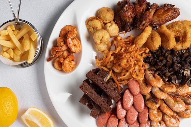 Anéis de cebola fritos, lulas à milanesa, batatas crocantes, limão e salsichas grelhadas