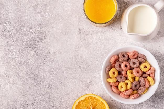 Anéis de cereais coloridos na tigela e leite