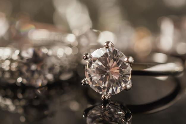 Anéis de diamante com reflexo no fundo preto