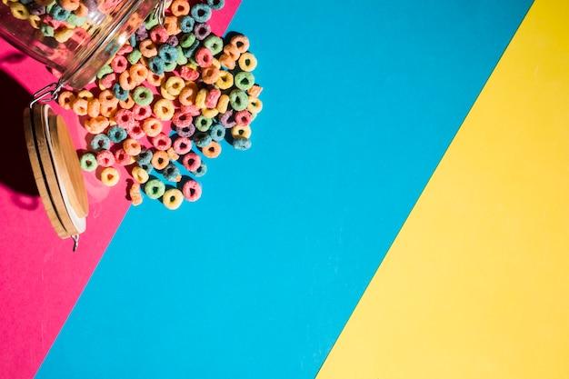 Anéis de laço de cereais coloridos derramando de jar no pano de fundo colorido