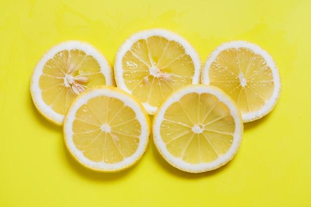 Anéis de limões frescos fatiados em fundo amarelo brilhante