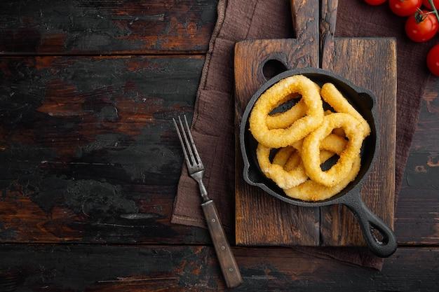 Anéis de lula crocantes em migalhas de pão colocados na frigideira de ferro fundido, no fundo da velha mesa de madeira escura, vista superior plana, com espaço de cópia para o texto