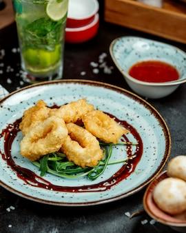 Anéis de lula fritos crocantes, guarnecidos com rúcula e molho teriyaki