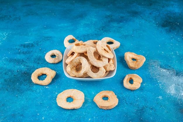 Anéis de maçã seca em uma tigela, na mesa azul.