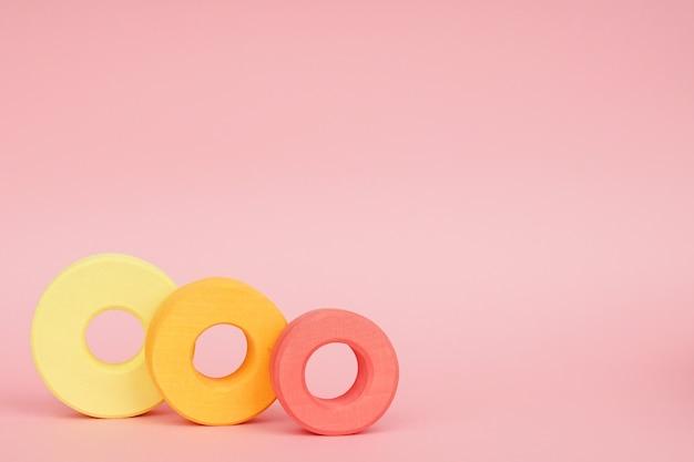 Anéis de madeira infantil de laranja e amarelo em um fundo rosa