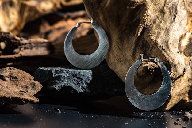 Anéis de metal moderno na raiz e fundo de pedra preta com efeito de luz dura