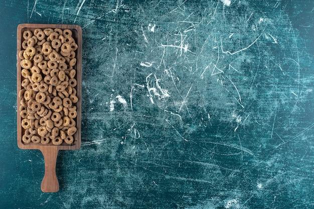 Anéis de milho de chocolate em uma placa, na mesa azul.