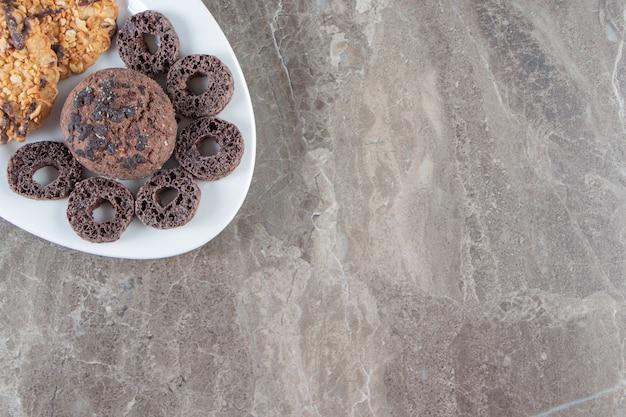 Anéis de milho e biscoitos caseiros em um prato de mármore.