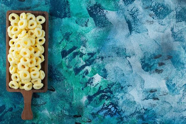 Anéis de milho em uma placa, na mesa azul.