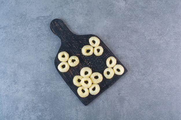 Anéis de milho em uma tábua de corte, na superfície de mármore