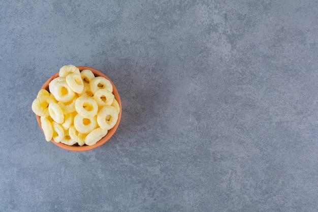 Anéis de milho em uma tigela de barro, na superfície de mármore