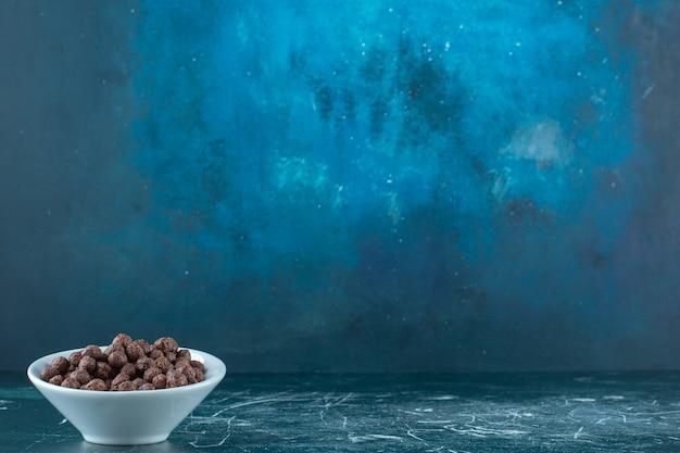 Anéis de milho em uma tigela na superfície azul