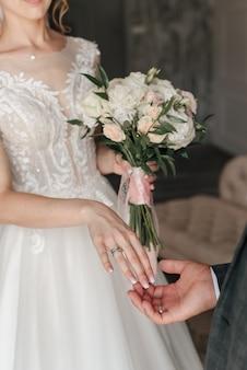 Anéis de noiva e noivo e buquê