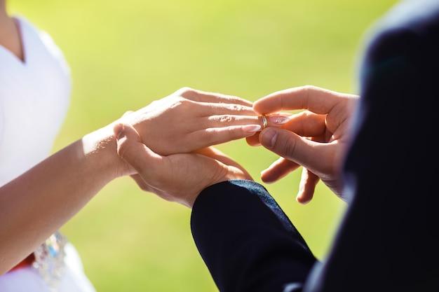 Anéis de noivado de casamento. o casal troca alianças de casamento em uma cerimônia de casamento. noivo colocou um anel no dedo de sua adorável esposa. detalhes do casamento de conceito. família feliz. juntos.
