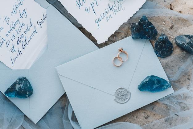 Anéis de noivado e casamento em um envelope ao lado do convite e menu