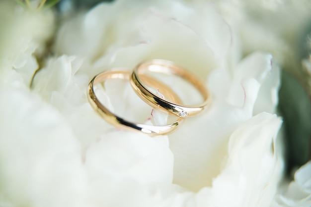 Anéis de noivado e flores, buquê de casamento fundo, foco seletivo, macro